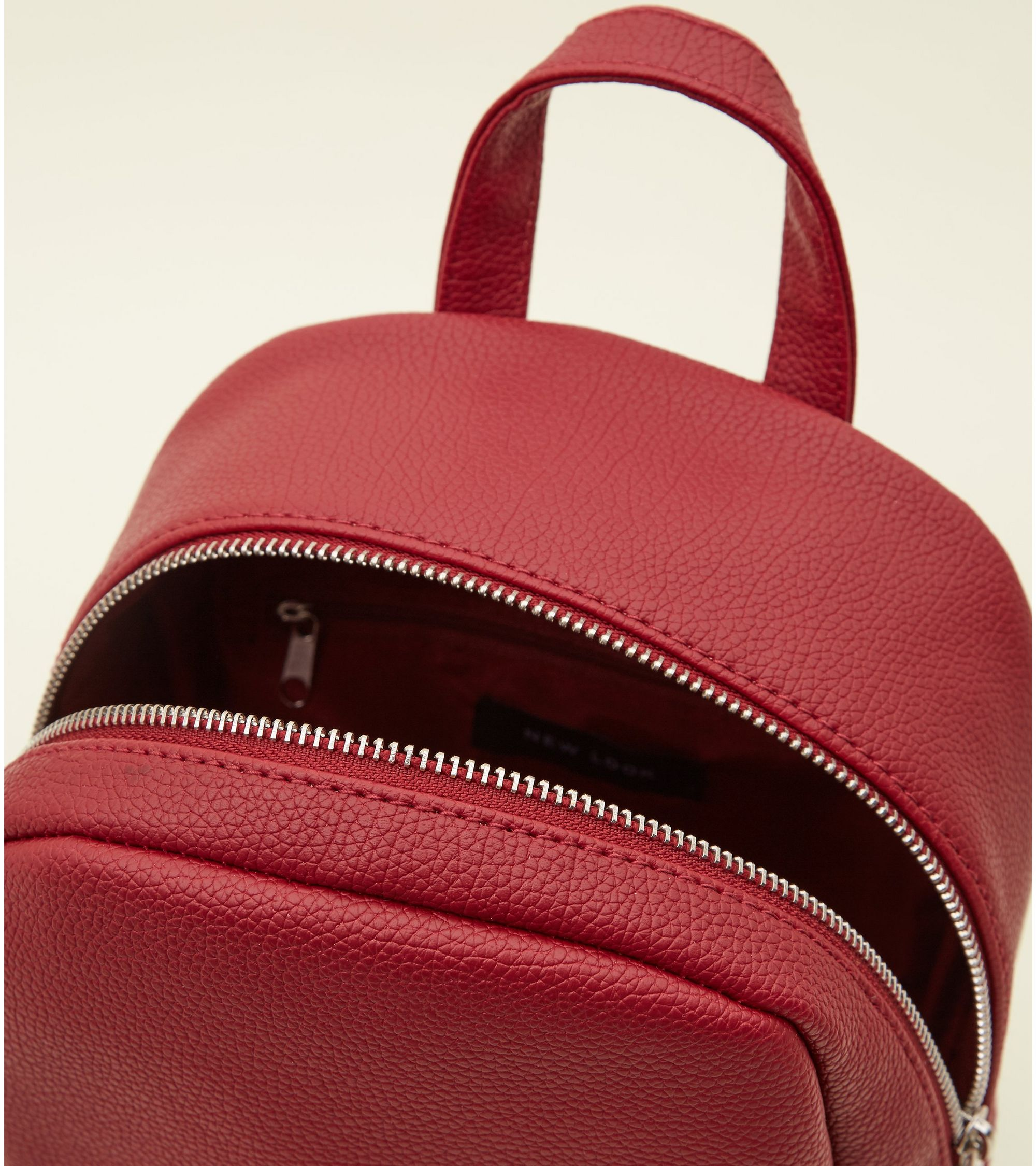 dcf4101771 New Look Dark Red Zip Top Curved Mini Backpack at £19.99