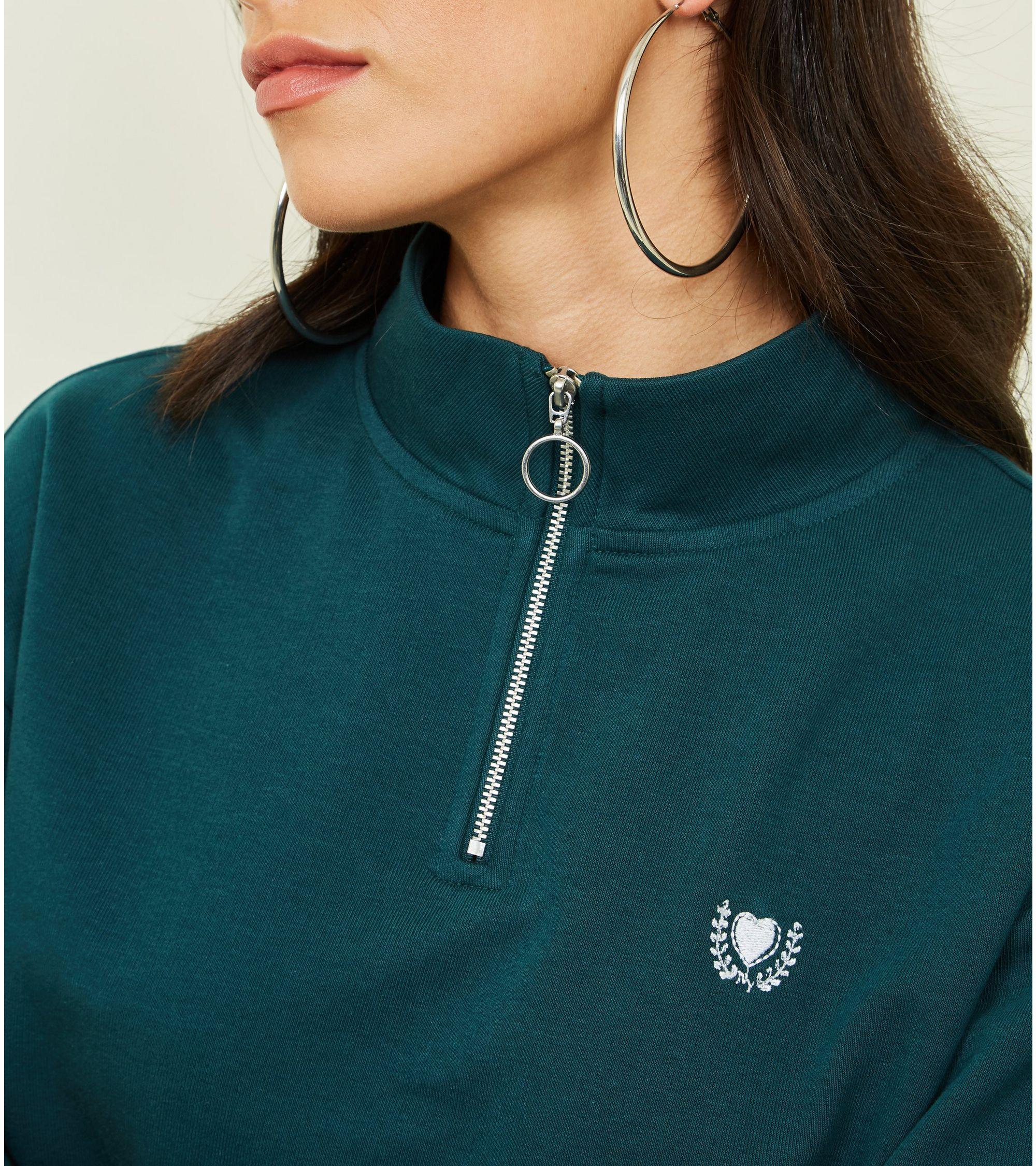 d0ded801835c New Look Dark Green Heart Crest Zip Neck Sweatshirt at £17.99